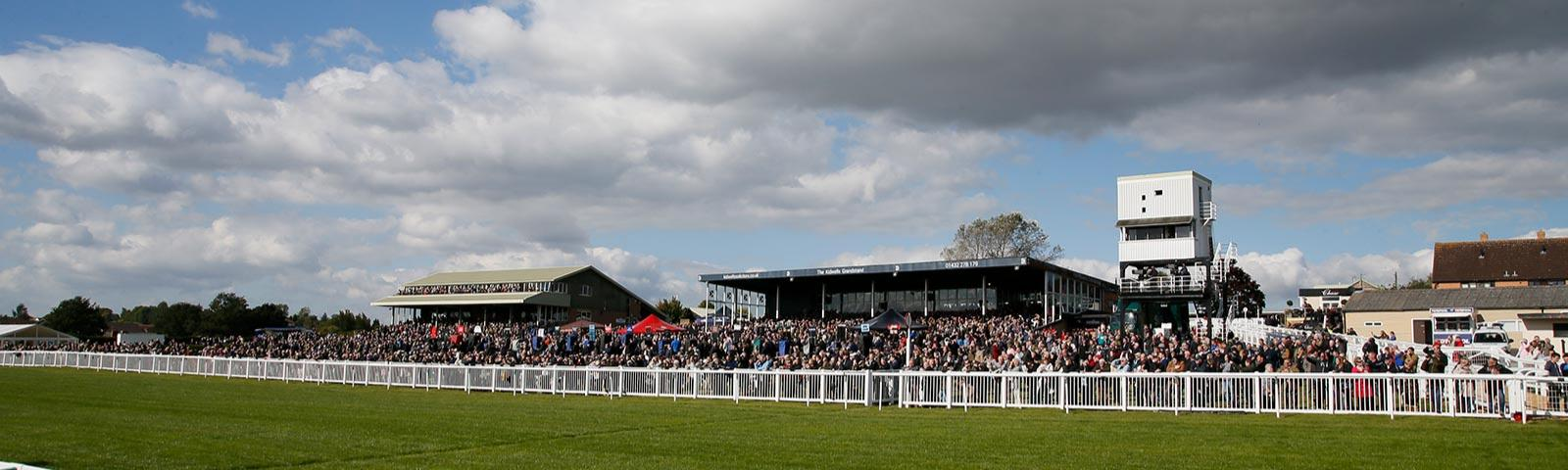 Crowds watching the racing action at Hereford Racecourse.
